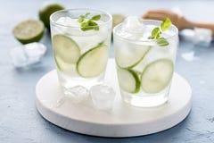 健康柠檬水石灰用新鲜薄荷和冰在一块玻璃在蓝色水平背景鲜美自创戒毒所水被灌输的水 图库摄影
