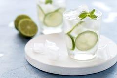 健康柠檬水石灰用新鲜薄荷和冰在一块玻璃在蓝色背景鲜美自创戒毒所水灌输了水接近  免版税库存图片