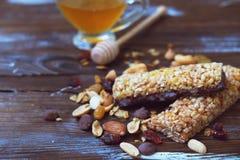 健康格兰诺拉麦片棒用干果子、坚果和蜂蜜在木背景 免版税库存图片