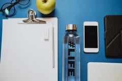 健康桌面:笔记本,铅笔,水,苹果,电话,玻璃 免版税图库摄影