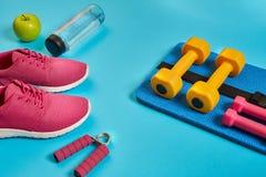 健康概念、饮食计划与体育鞋子和瓶水和哑铃在蓝色背景,健康食物和 免版税库存照片