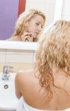 健康概念和想法 在卫生间里检查她的在镜象反射的白种人妇女画象粉刺有倾向的皮肤 免版税库存照片