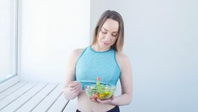 健康概念的食物 吃健康蔬菜沙拉的愉快的妇女在白色内部的锻炼以后 股票录像