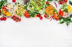 健康概念的食物 菜在塑料包裹的色拉盘品种在白色木背景,顶视图,边界 沙拉ba 库存照片