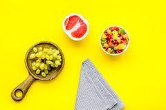 健康概念的饮食 在新鲜水果附近的水果沙拉在黄色背景顶视图 库存图片