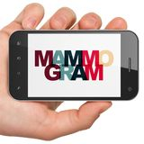 健康概念:拿着有乳房X线照片的手智能手机在显示 免版税库存图片
