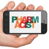 健康概念:拿着有药剂师的手智能手机显示的 免版税图库摄影