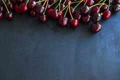 健康樱桃在黑色板岩结果实,被隔绝 免版税图库摄影