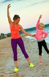 健康母亲和女儿海滩的在晚上舒展 免版税库存图片