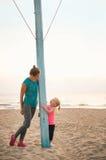 健康母亲和女婴海滩的在晚上 免版税图库摄影