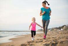健康母亲和跑在海滩的女婴 免版税图库摄影