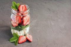 健康沙拉盘用新鲜的草莓、芝麻菜和软干酪在玻璃瓶子 库存照片
