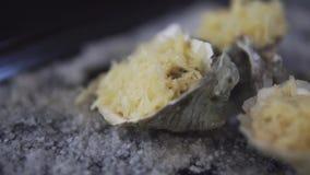 健康海鲜,特写镜头新鲜的开放牡蛎用在一个烤板的乳酪与盐 股票录像
