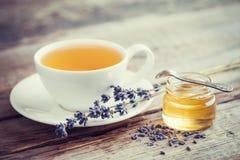健康淡紫色茶杯、瓶子蜂蜜和淡紫色开花 免版税图库摄影