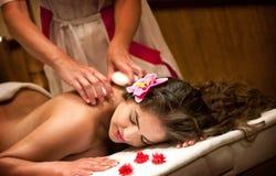 健康温泉:有年轻美丽的松弛的妇女石按摩 免版税库存图片