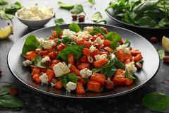 健康烤地瓜土豆沙拉用菠菜,希腊白软干酪,在黑色的盘子的榛子坚果 免版税库存照片
