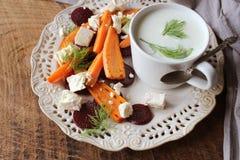 健康烤甜菜、红萝卜沙拉用乳酪希脂乳,茴香和希腊酸奶在小玻璃碗在土气木桌,上面上 库存图片