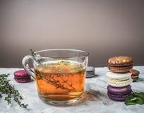 健康热的清凉茶用莓果、麝香草和薄菏,开胃,多彩多姿的蛋白杏仁饼干,堆在白色土气背景,空间 库存照片