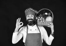 健康烹调概念 厨师拿着圆白菜、萝卜、硬花甘蓝和莴苣 免版税图库摄影