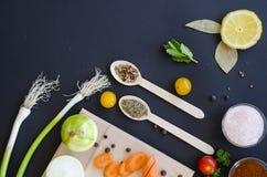 健康烹调的新鲜的可口做在深黑色背景和木切板的成份或沙拉 免版税库存照片
