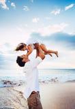 健康爱恋的一起使用在海滩的父亲和女儿 免版税库存图片