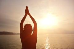 健康瑜伽妇女凝思在日出海边 免版税图库摄影