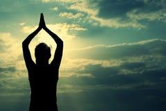 健康瑜伽妇女凝思在日出海边 免版税库存照片