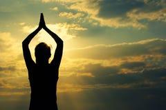 健康瑜伽妇女凝思在日出海边 免版税库存图片