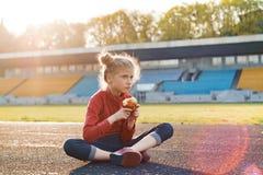 健康生活方式和健康食物概念 运动服的小美女孩子吃苹果的以后坐体育场 免版税库存照片