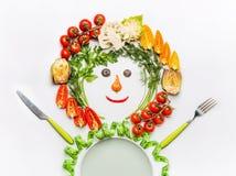 健康生活方式和节食的概念 友好的人由沙拉菜、板材、利器和测量的磁带制成在白色书桌 免版税库存图片