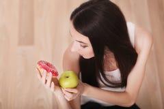 健康生活方式或营养概念与拿着在手上一个绿色苹果和多福饼的少妇 免版税图库摄影