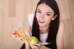 健康生活方式或营养概念与拿着在手上一个绿色苹果和薄饼的少妇 免版税库存图片