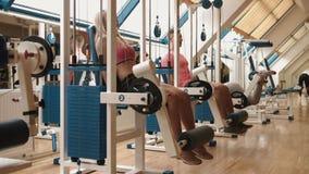 健康生活方式概念 年轻运动夫妇在健身房解决 在腿卷毛教练员的快的训练 股票录像
