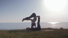 健康生活方式,瑜伽对在享受自然,在海背景的新鲜空气的草甸做着锻炼  股票录像