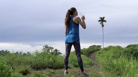 健康生活方式 在跑步期间的运动的妇女饮料水在自然公园 影视素材