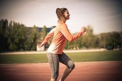 健康生活方式 美丽的白种人中国女性混合的族种赛跑者运行中线索火山妇女 黑色接近的耳机图象软绵绵地查出话筒填充白色 图库摄影