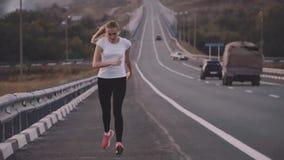 健康生活方式 运行在城市之外的一双白色T恤杉和明亮的运动鞋的一位年轻运动员 在背景  影视素材