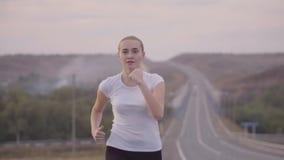 健康生活方式 运行在路的一件白色T恤杉的一个女孩从城市在日落,振翼在风的头发 股票录像