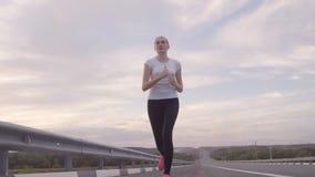 健康生活方式 运行在路的一双白色T恤杉和明亮的运动鞋的一个女孩从城市在日落,头发 股票视频