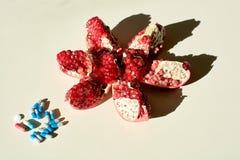 健康生活的概念 成熟红色水多的石榴和药片,胶囊,分别地说谎在白色背景的药片 免版税库存图片
