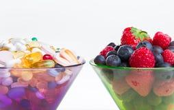 健康生活方式、饮食概念、果子和药片,维生素补充 免版税库存图片