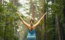 健康生活方式健身运动的妇女及早在森林区域 库存图片