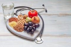 健康生活方式和医疗保健概念用食物、心脏和听诊器 库存照片