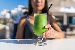 健康生活方式妇女饮用的咖啡馆绿色汁 免版税库存图片