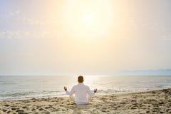 健康生活方式概念-供以人员做瑜伽在海滩的凝思锻炼 免版税图库摄影