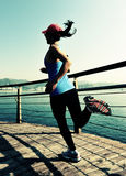 健康生活方式炫耀跑在木木板走道的妇女 图库摄影