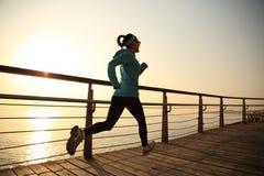 健康生活方式炫耀跑在unrise海边的妇女 免版税库存图片