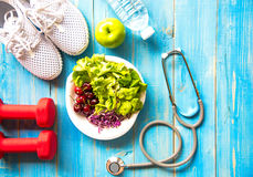 健康生活方式运动器材健身、运动鞋、绿色苹果、淡水和健康食物在蓝色木背景 免版税库存图片