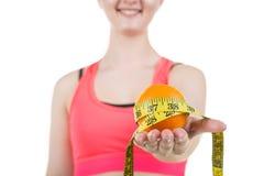 健康生活方式,健康吃 一个女孩拿着一个桔子和一卷测量的磁带,在白色背景 水平的框架 免版税库存图片