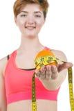 健康生活方式,健康吃 一个女孩拿着一个桔子和一卷测量的磁带,在白色背景 水平的框架 免版税库存照片